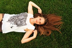 Young beautiful girl lying on a green lawn. Young beautiful girl is lying on a green lawn . She has expressive eyes and long hair Royalty Free Stock Photo