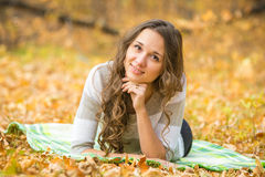 Young beautiful girl lying on a rug in the autumn forest Royalty Free Stock Images