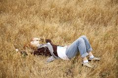 Young beautiful girl lying at yellow autumn field. Stock Images