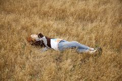 Young beautiful girl lying at yellow autumn field. Stock Photos