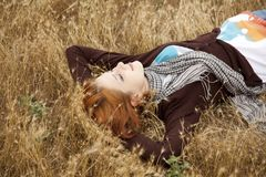 Young beautiful girl lying at yellow autumn field. Royalty Free Stock Photography