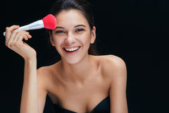 Young beautiful girl with make up pink brush on black background. Stock Photography