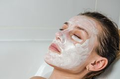 Young beautiful girl makes a white face mask for beauty during spa treatments in the bathroom Royalty Free Stock Image