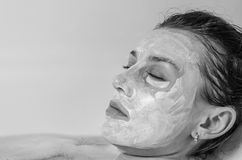 Young beautiful girl makes a white face mask for beauty during spa treatments in the bathroom Stock Photo