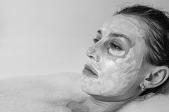 Young beautiful girl makes a white face mask for beauty during spa treatments in the bathroom Royalty Free Stock Photos