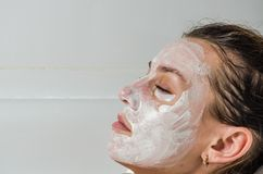 Young beautiful girl makes a white face mask for beauty during spa treatments in the bathroom Royalty Free Stock Photography