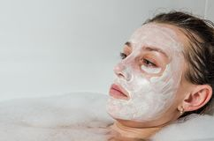 Young beautiful girl makes a white face mask for beauty during spa treatments in the bathroom Stock Images