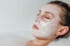 Young beautiful girl makes a white face mask for beauty during spa treatments in the bathroom Stock Image