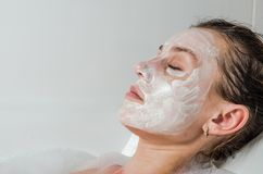 Young beautiful girl makes a white face mask for beauty during spa treatments in the bathroom Stock Photos