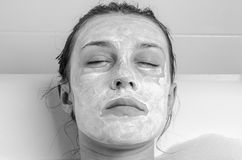 Young beautiful girl makes a white face mask for beauty during spa treatments in the bathroom Stock Photography