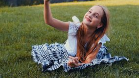 Young beautiful girl making selfie portrait using smartphone in green park, lying on the grass with mobile phone. Color stock footage