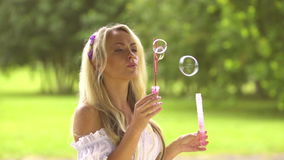 Young and beautiful girl making soap bubbles outdoors.