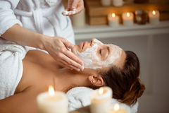 Young beautiful girl in mask for face relaxing in spa salon. Stock Photography