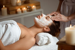 Young beautiful girl in mask for face relaxing in spa salon. Royalty Free Stock Images