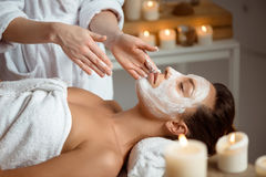 Young beautiful girl in mask for face relaxing in spa salon. Royalty Free Stock Image