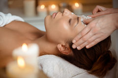 Young beautiful girl in mask for face relaxing in spa salon. Stock Images