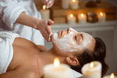Young beautiful girl in mask for face relaxing in spa salon. Stock Image