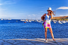 Young beautiful girl on the mediterranean sea quay. Young beautiful girl in panama cap and sunglasses and hairs on the wind on the sunny mediterranean sea quay Royalty Free Stock Images