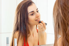 Young beautiful girl before the mirror does makeup Stock Photos
