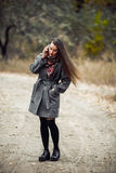 Young beautiful girl with mobile phone walking in the park Royalty Free Stock Photo