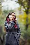 Young beautiful girl with mobile phone walking in the park Stock Images