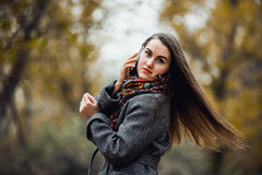 Young beautiful girl with mobile phone walking in the park Royalty Free Stock Photos