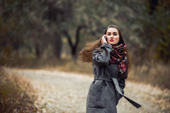 Young beautiful girl with mobile phone walking in the park Royalty Free Stock Photography
