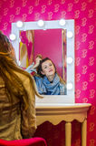 Young beautiful girl model in a denim jacket and a scarf sits at a table in front of a mirror with lamps and makes a make-up befor Stock Photo