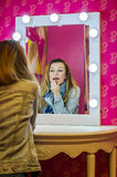 Young beautiful girl model in a denim jacket and a scarf sits at a table in front of a mirror with lamps and makes a make-up befor Royalty Free Stock Images