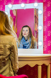 Young beautiful girl model in a denim jacket and a scarf sits at a table in front of a mirror with lamps and makes a make-up befor Stock Photography