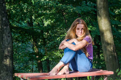 Young beautiful girl model in jeans and a T-shirt with long blond hair and sad smiles pensively posing for a walk in the autumn pa Royalty Free Stock Photography