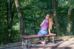 Young beautiful girl model in jeans and a T-shirt with long blond hair and sad smiles pensively posing for a walk in the autumn pa stock image