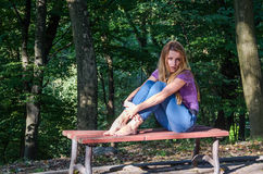 Young beautiful girl model in jeans and a T-shirt with long blond hair and sad smiles pensively posing for a walk in the autumn pa. Rk sitting on a bench among Royalty Free Stock Photography