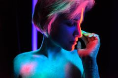 Model young beautiful girl portrait in studio with creative makeup, in neon ultraviolet lamp. Glows in the dark. Hair. Young beautiful girl model with short Royalty Free Stock Image