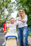 Young beautiful girl mother rolls her daughter with a bow on her head, which is show your laughing two teeth on a swing in amuseme Stock Photos