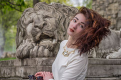 Young beautiful girl near the statue of a stone lion during a walk in the city of Lviv stock photography