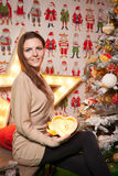 Young beautiful girl in the New Year decorations on the background of wallpaper with colorful people Stock Images