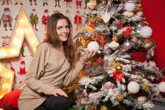 Young beautiful girl in the New Year decorations on the background of wallpaper with colorful people Stock Photography
