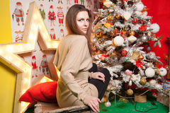 Young beautiful girl in the New Year decorations on the background of wallpaper with colorful people Royalty Free Stock Photo