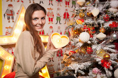 Young beautiful girl in the New Year decorations on the background of wallpaper with colorful people Stock Photo