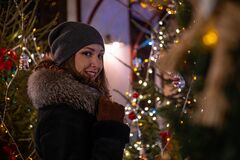 Young beautiful girl in new year decorations on the street in winter Christmas holidays