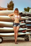 Young beautiful girl at old surfing and windsurfing station stands near the surfboards installed on the racks outdoor royalty free stock images
