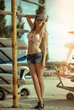 Young beautiful girl at old surfing and windsurfing station stands near the surfboards installed on the racks outdoor stock photos