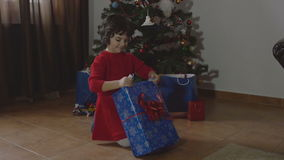 Young beautiful girl opening the Christmas present - 4k. Young beautiful girl opening the Christmas present 4k stock footage