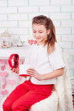 Young beautiful girl opening present box. And smiling; studio portrait in valentines decorations Royalty Free Stock Image