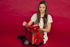 Young beautiful girl opens her christmas gift Royalty Free Stock Images