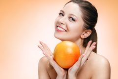 Young beautiful girl with orange Royalty Free Stock Photography