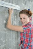 Young beautiful girl with pallets stay near the repaired wall Stock Image