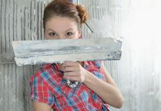 Young beautiful girl with pallets stay near the repaired wall Royalty Free Stock Photo
