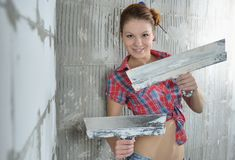 Young beautiful girl with pallets stay near the repaired wall Royalty Free Stock Photos